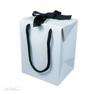 Weiße Geschenkbox aus Papier mit Schleife und Henkeln